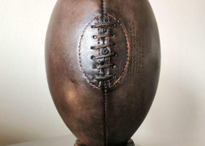 Un ballon de rugby vintage posé sur un socle en bois