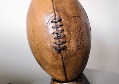 Un ballon de rugby vintage sur un tee en bois