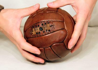 Mini ballon de foot tenu dans des mains d'un jeune homme