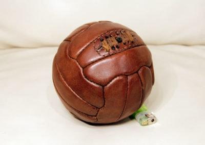 Mini ballon de foot vintage posé à coté d'un briquet pour se rendrecompte de la taille.