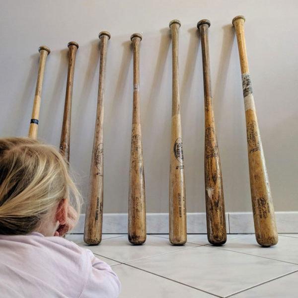 lot anciennes battes de baseball présentées au sol devant une fille