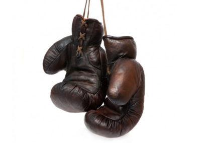 Une paire de gants de boxe vintage John Woodbridge marron accrochés sur fond blanc