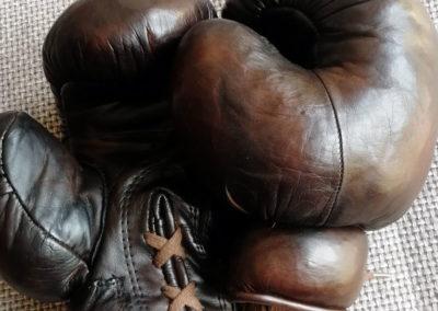 Une paire de gants de boxe vintage John Woodbridge marron posés sur un canapé à la lumière