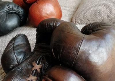 Une paire de gants de boxe vintage John Woodbridge marron posés sur un canapé à côté d'autres couleurs de gants de boxe