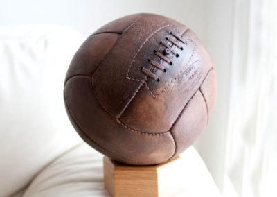 les lacets d'un vieux ballon de foot exposé à la lumière du jour