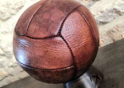 Présentation du ballon de foot ancien sur un socle foncé