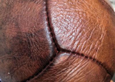 une vue macro des coutures d'un vieux ballon de rugby en cuir havane