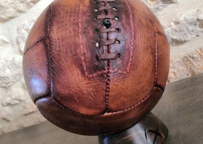 Présentation d'un ancien ballon de foot vintage avec lacets sur un socle foncé