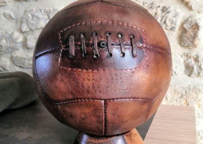 Un ballon de foot ancien présenté en décoration sur un meuble