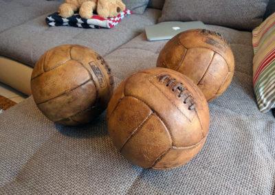 3 ballons anciens présentés sur un canapé