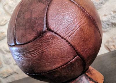 Présentation du ballon de foot ancien sur un socle clair