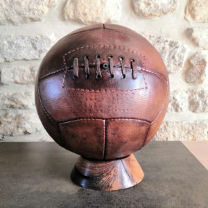 Un ballon de foot en cuir posé sur un socle en décoration sur un meuble