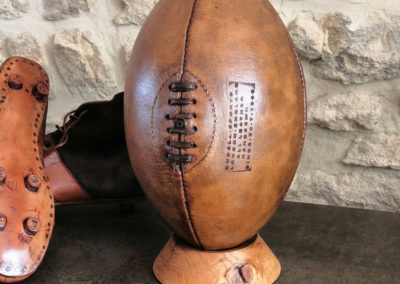 allon de rugby présenté avec des chaussures crampons