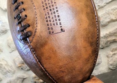 Mise en valeur de la vieille patine d'un vieux ballon de rugby sur son socle en bois