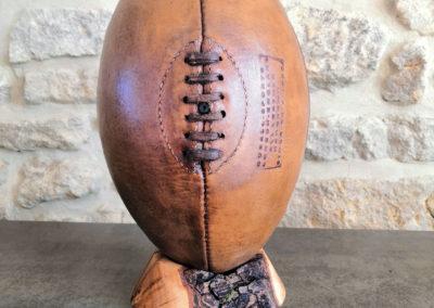 Un ancien ballon de rugby de couleur havane présenté sur son socle en bois
