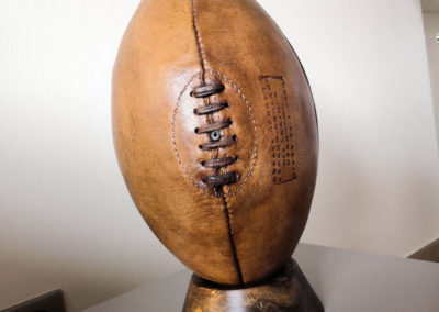 Le ballon de rugby vintage est présenté sur le socle foncé couleur exotique