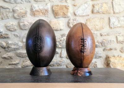 Deux ballons de rugby anciens sont présentés l'un à côté de l'autre sur leur socle pour pouvoir comparer la couleur