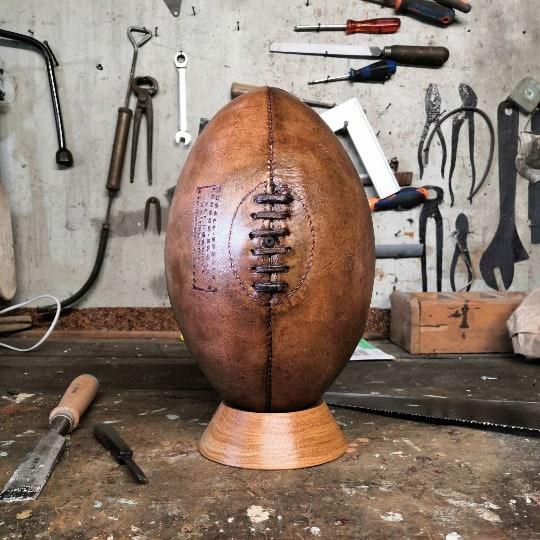Ancien ballon de rugby présenté dans un atelier avec des outils