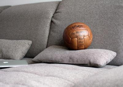 Une pose paisible d'un ancien ballon de football soccer sur un coussin de canapé