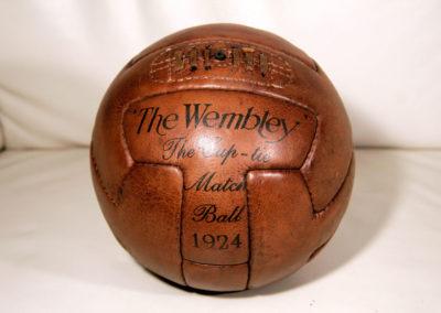 Un ancien ballon de football couleur miel posé sur un canapé en cuir