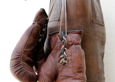 Anciens gants de boxe de couleur brune accrochés à un gros sac de frappe à l'extérieur