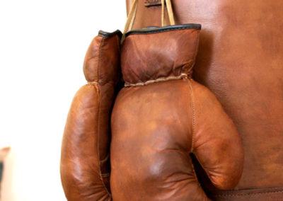 Gants de boxe vintage de couleur camel accrochés à un gros sac de frappe vintage