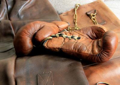Une paire de gants de boxe ancienne présentées à lalumière sur du cuir