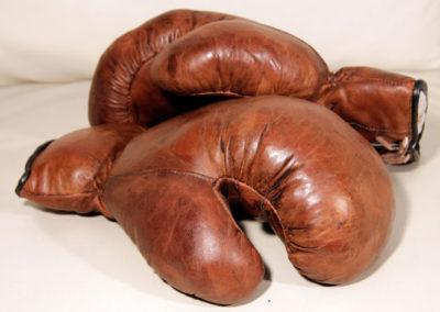 Anciens gants de boxe vintage magnifiques sur leur canapé en cuir
