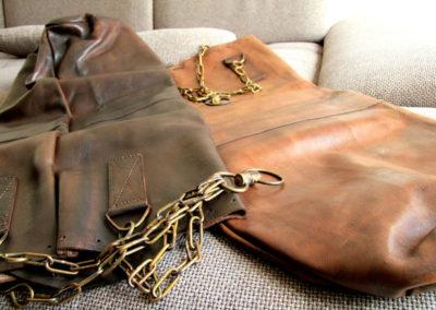 2 sacs de frappes de 2 cuirs différents posés sur un canapé