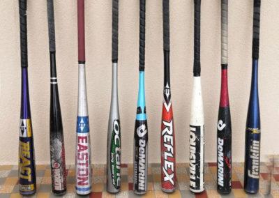 9 battes de baseball anciennes en alu posées debout contre un mur