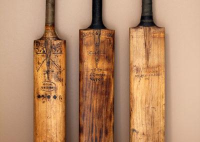 3 battes de cricket anciennes posées contre un mur camel d'un salon