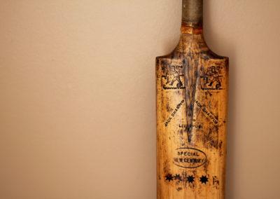 Ancienne batte de cricket avec marquage adossée à un mur havane pour la décoration