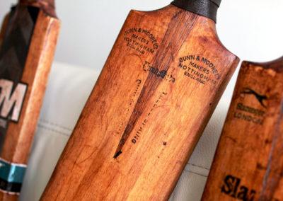 Une batte de cricket ancienne posée sur le canapé