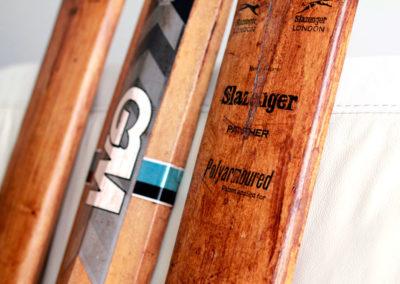 Une batte de cricket ancienne à côté d'une plus moderne colorée