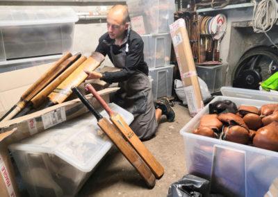 Ben porte un lot de battes de cricket en bois à l'atelier