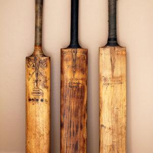 3 battes de cricket anciennes posées contre un mur camel