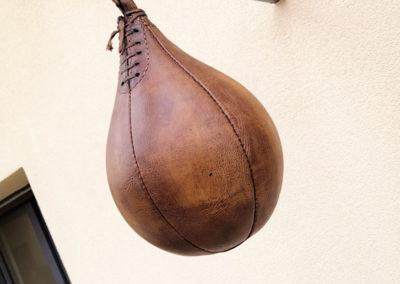 Un ancien speedball vintage en cuir accroché sous une véranda