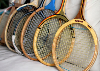 lot anciennes raquettes de badminton posé sur un canapé en cuir