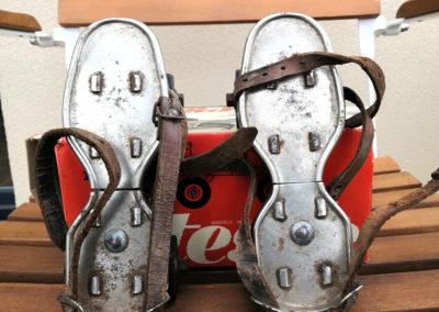 Ancienne paire de patins à roulette posée sur une siège en bois