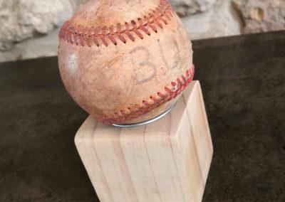 Une balle de baseball ancienne agnifique présentée sur un petit socle en bois