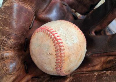 Une balle de baseball présentée dans un gants de baseball en cuir