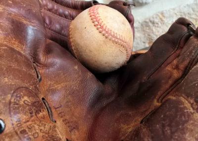 Une balle de baseball au fond de son gant en arrière plant