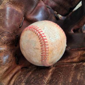 Présentation dans son gant en cuir d'une ancienne balle de baseball vintage