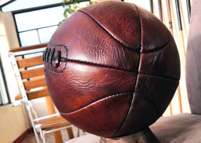 Présentation d'un vieux ballon de basket plein sud au soleil