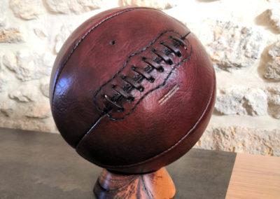 Un vieux ballon de basket posé sur un socle en chêne