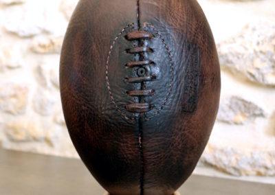 Ballon de rugby en cuir présenté sur un fond très clair tout comme son socle afin de montrer une déco vintage