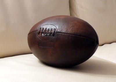 Ballon de rugby en cuir posé sur un canapé clair