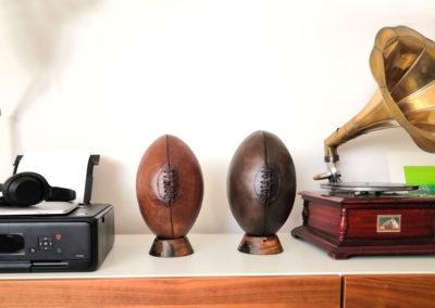 2 ballons de rugby en cuir présentés sur une déco vintage