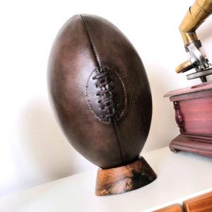 Ancien ballon de rugby en cuir présenté sur un socle rugby (tee)