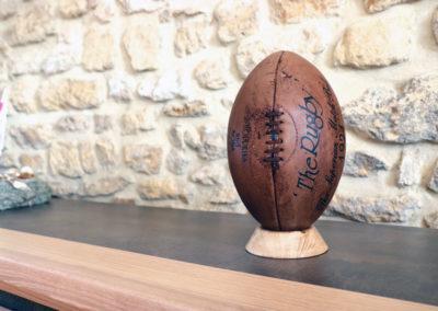 Le ballon de rugby vintage est présenté sur son socle clair en chêne